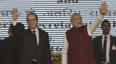 Francois Hollande and Narendra Modi wave at the audience as they arrive for the foundation stone laying for the headquarters of the International Solar Allliance at Gurgaon.