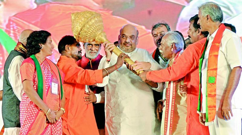 State BJP leaders present a mace to party president Amit Shah during a public meeting at the Jawaharlal Nehru Stadium in Hanamkonda on Saturday to mark the Hyderabad Liberation Day. Union minister Bandaru Dattatreya, party state chief K. Laxman and other leaders are also seen. (Photo: DC)