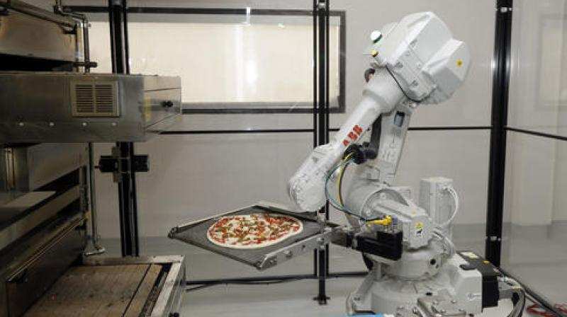 A robot places a pizza into an oven at Zume Pizza in Mountain View, Calif. The Silicon Valley startup is using robots to grab a slice of the $10 billion pizza-delivery business. Zume Pizza is building intelligent machines to automate the production and delivery of artisan pizzas. (AP Photo/Marcio Jose Sanchez)
