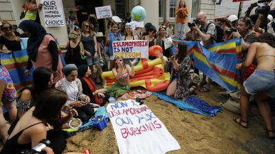 Brandishing beach balls, towels and inflatables, around 50 people protested against the burkini ban in France Thursday by creating a fake beach outside the country's embassy in London.