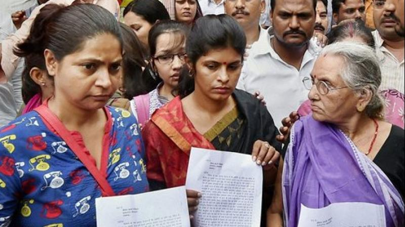Expelled BJP leader Daya Shankar Singh's mother (R), wife Swati Singh (C) and others after filing a complaint against Mayawati and other BSP leaders at a police station. (Photo: PTI)