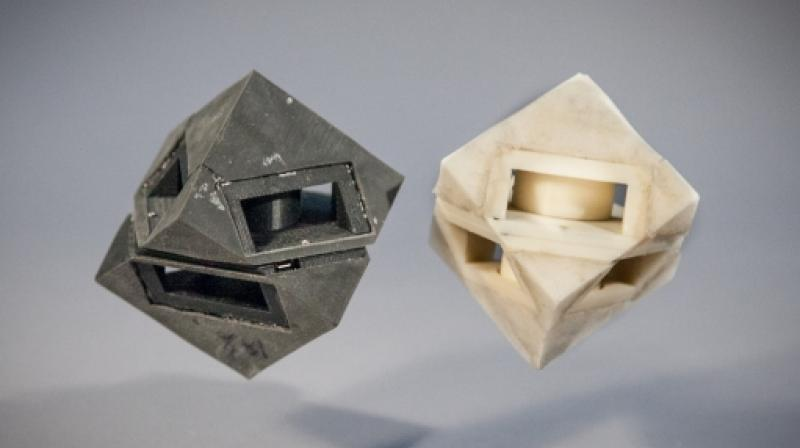 """MIT researchers outfitted their cube robot with shock-absorbing """"skins"""" (left) that transfer less than half of the energy that would normally be transferred to the ground.  Photo: Jason Dorfman/MIT CSAIL"""