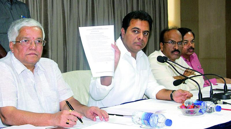 Minister K.T. Rama Rao displays the 100-day agenda.