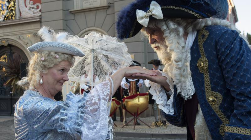 A man dressed in a Baroque costume greets a woman in front of the city hall during the opening of the Baroque Festival in Gotha, Germany. For 13 years the city of Gotha changes completely into a baroque city in order to celebrate the Baroque Festival around the Friedenstein Castle, the biggest German early Baroque palace complex from the 17th century.
