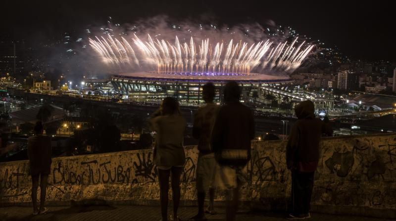 The curtains came down on the 2016 Rio Olympic Games on Sunday. This picture, people of the Mangueira slum watch the Olympics closing ceremony at the Maracana stadium in the distance.