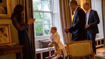 Prince George sits on the rocking chair gifted to him by Barack Obama. On Friday, Obama and his wife Michelle flew to Queen Elizabeth's castle to wish happy birthday to the world's oldest monarch a day after she turned 90, calling her one of his favourite people and a personal inspiration.