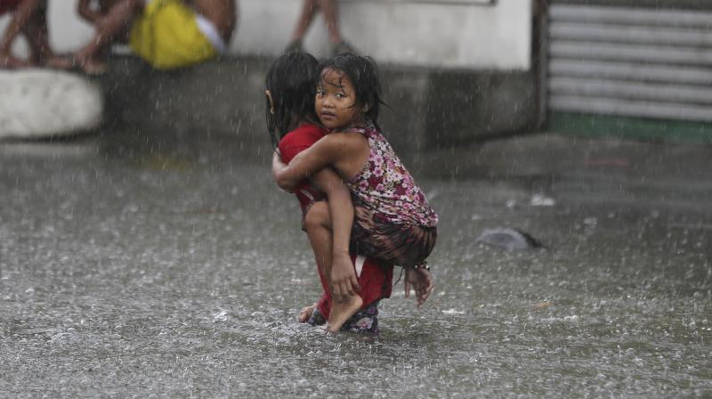 A girl is carried along a flooded road in suburban Mandaluyong, east of Manila, Philippines, as monsoon downpours intensify while Typhoon Nepartak leaves the country.