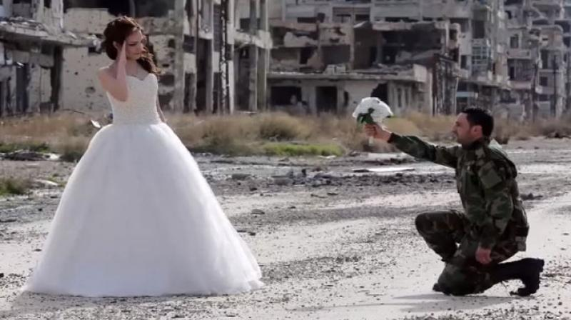 Although the ongoing civil war in Syria has greatly damaged the city, one couple decided to celebrate their happiness against this backdrop of colossal destruction. (YouTube/ Screen grab)