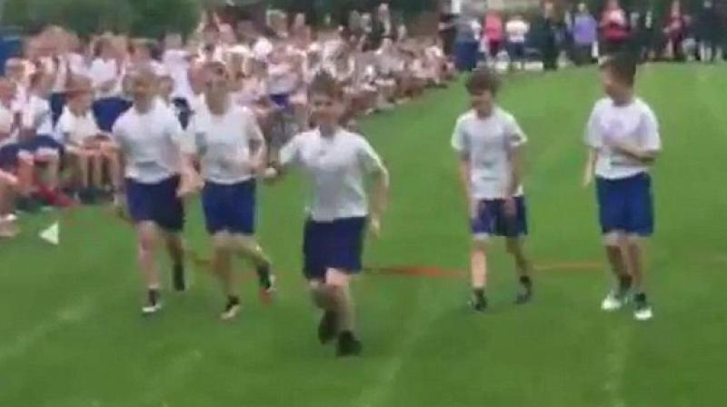 Daniel Boyers, 10, won the gold medal on his school's sports day after his friends slowed down for him. (Credit: YouTube)