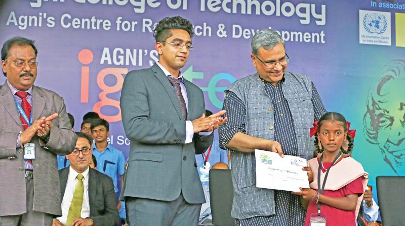 Rajiv Chandran, Chief, United Nations Information Centre for India and Bhutan hands over the certificate to M. Kavya.  (Second from left) Agnishwar, executive director, Agni group of institutions also looks on. (Photo: DC)
