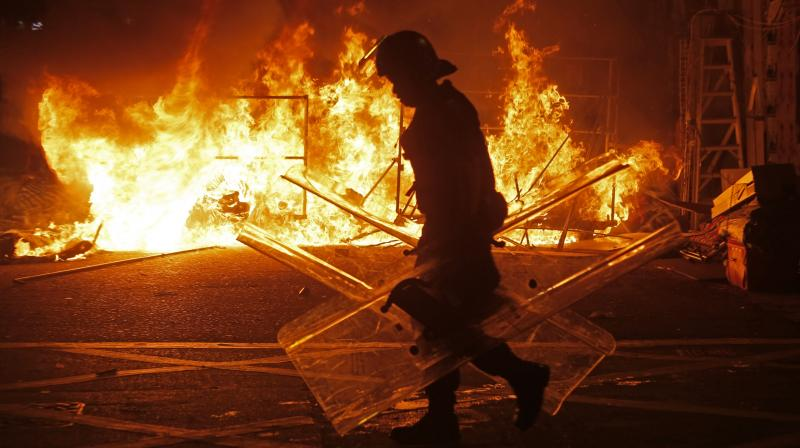 A police officer walks past fire set by rioters in Mong Kok district of Hong Kong.