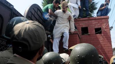 Kashmir's chief Muslim cleric and separatist leader, Mirwaiz Umar Farooq, scales the outer wall of his besieged residence in Srinagar's Nigeen area in an attempt to march on the City's Mazar-e-Shohda or martyrs' cemetery to pay home to the 1931 martyrs.