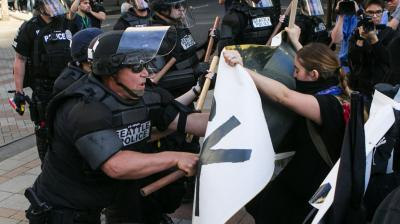 Five Seattle police officers were injured and at least nine people arrested on Sunday night, after unruly demonstrators hurled projectiles and Molotov cocktails and broke windows, authorities said.