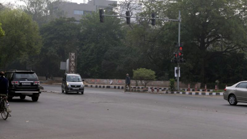 Amitabh crosses a busy street in Delhi without being noticed.