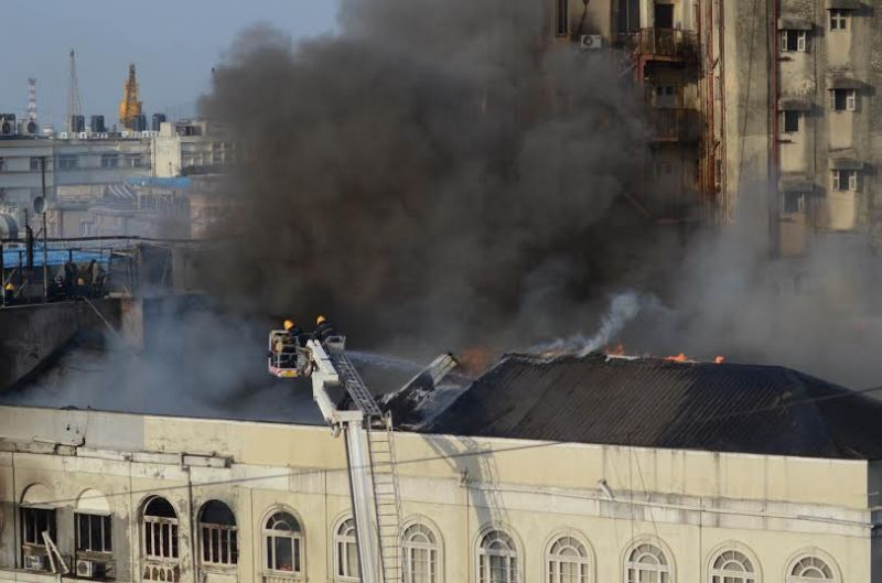 Firemen busy trying to bring the fire under control at the roof of the building. (Photo: DC/Sripad Naik)