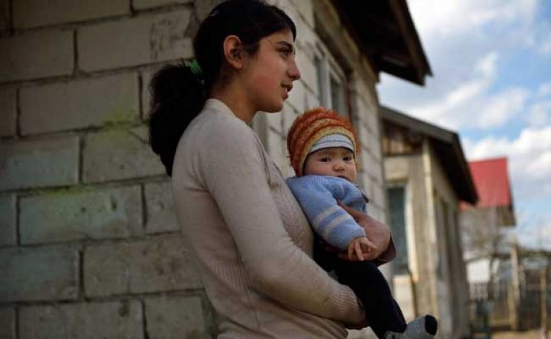 15-year-old Diana holds her child at their home in a village near Botosani. (Photo: AFP)