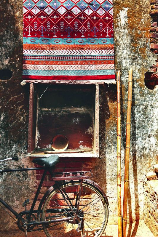 A villager's cycle parked beneath one of the rugs woven for the collection.