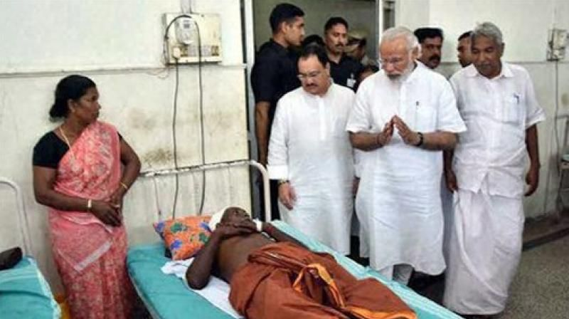 Modi visiting the victims of the temple tragedy.
