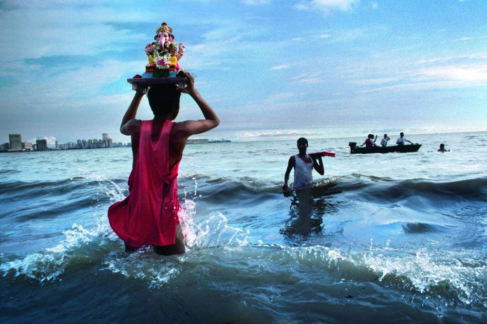 Devotee carries statue of Lord Ganesh into the waters of the Arabian Sea during the immersion ritual off Chowpatty beach, Mumbai, 1993