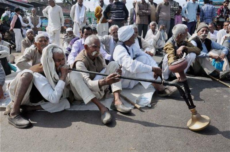 Members of the Jat community, under the banner of Bharatiya Kisan Union, block traffic demanding reservation, in Rajabpur village of Amroha district. (Photo: PTI)