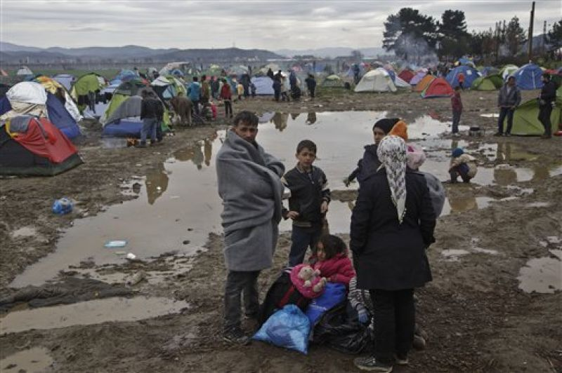 A family stand near a puddle of mud at the Greek border camp near Idomeni. (Photo: AP)