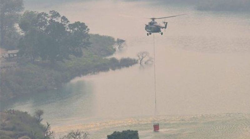 Indian Air Force Helicopter collects water from Koteshwar dam during the rescue operation to control fire which broke out in the forests of Garhwal range in Uttrakhand. (Photo: PTI)