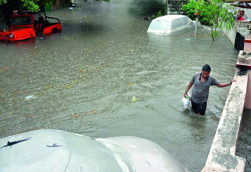 Four-wheelers are submerged as a man wades through a residential area in Nallakunta.