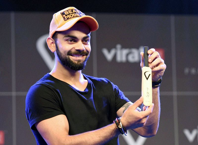 Virat Kohli also posed with an autographed bat signed by him that will be available inside the Virat Fan Box. (Photo: PTI)