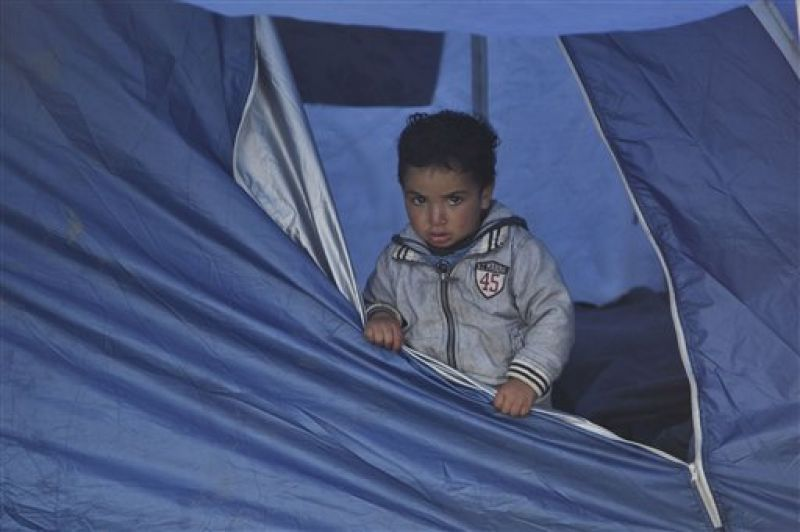 A migrant child takes shelter from the rain at the Greek border camp. (Photo: AP)