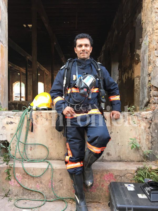Proud to wear the fireman's uniform, Randeep Hooda smiles as he poses for pictures