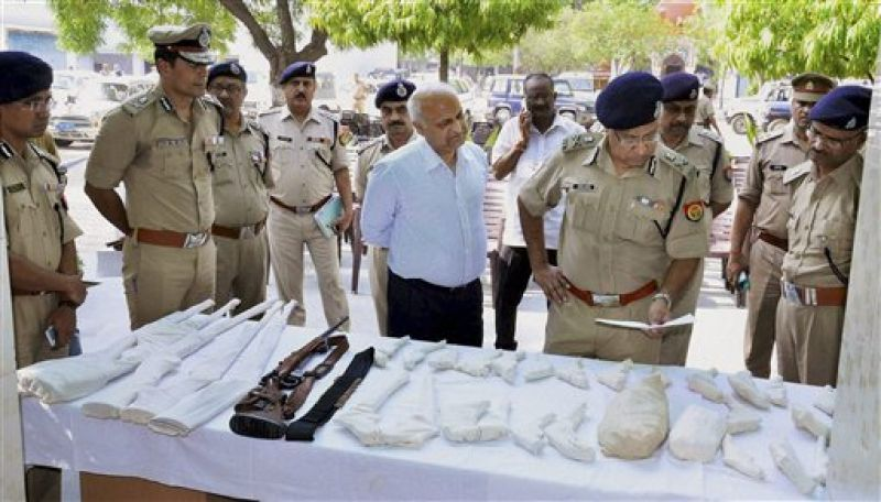 DGP Javed Ahmed look at the arms recovered from the Jawarhar Bagh encroachers, in Mathura. (Photo: PTI)