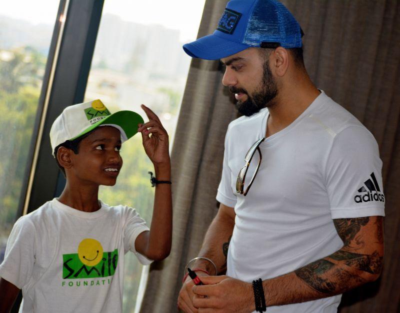 Virat Kohli sharing some batting tips with a Smile Foundation kid. (Photo: DC)
