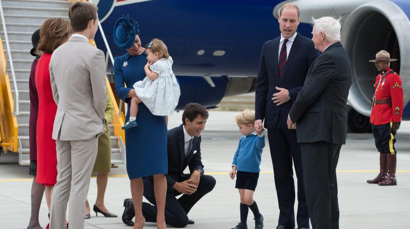 Canadian Prime Minister Justin Trudeau, center, kneels to talk to Prince George as his father Prince William speaks with Governor General David Johnston, right, and Kate holds their daughter Princess Charlotte upon arrival in Victoria, British Columbia, on Saturday.