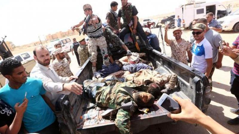 32 libya unity govt fighters die in car bomb clashes with isis libyan pro government forces and onlookers gather around the bodies of reported fighters of the sciox Choice Image