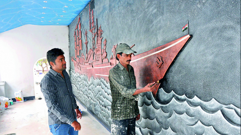 An artiste gives final touches to a mural in the museum in Visakhapatnam on Wednesday. (Photo: DC)