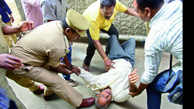 Police remove a protestor from the scene of the demolition on Thursday. Many tenants protested the GHMC move to demolish the Anand Bhavan