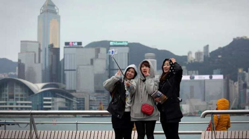 Three girls take a selfie as they brave the cold on a viewing deck next to Victoria Harbour in the Tsim Sha Tsui district of Hong Kong today. (Photo: AFP)