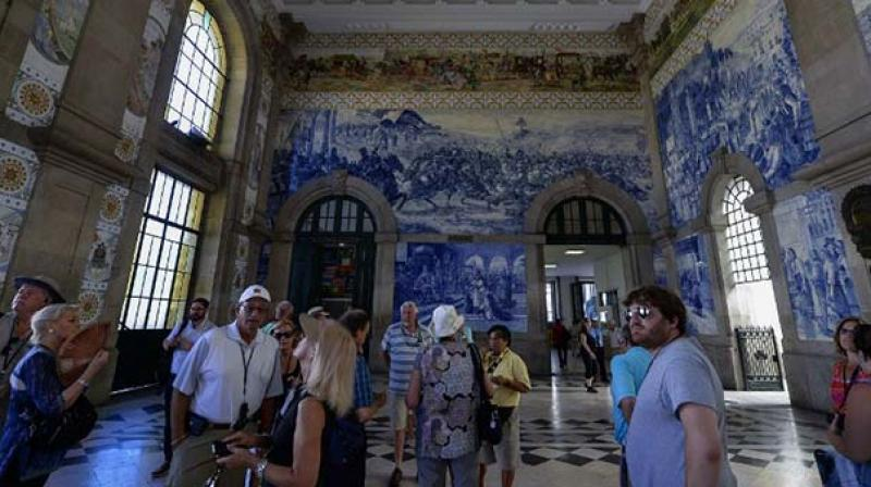 Tourists visit the Sao Bento railway station, in Porto. (Photo: AFP)