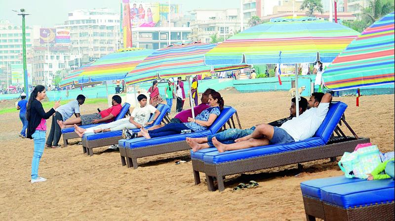 People relax on chairs with umbrellas which were set up for the visitors on the sands of Ramakrishna Beach in Visakhapatnam. (Photo: DC)