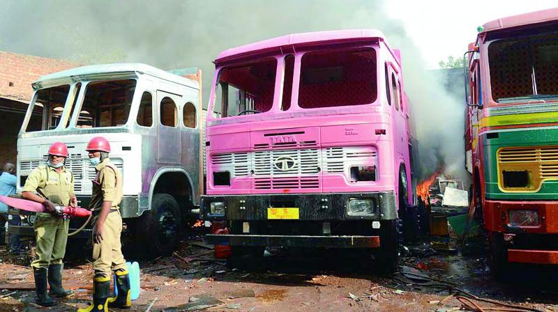 Fire service personnel douse the fire at the Sri Radha Krishna Lorry Body Building Works on Saturday. (Photo: DC)