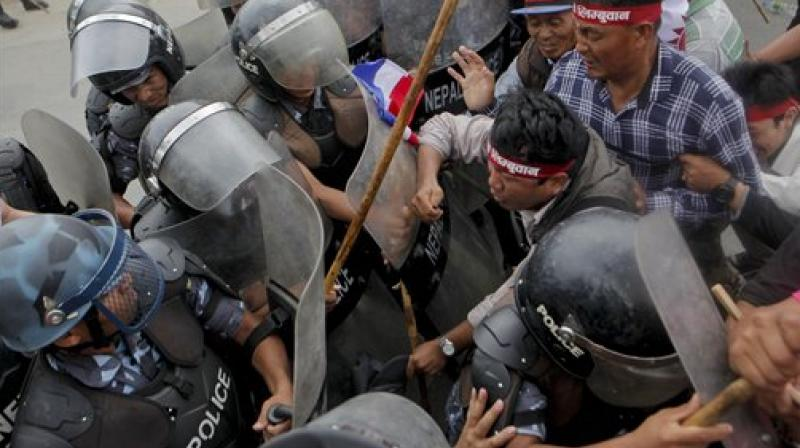 Supporters of Nepal's minority ethnic group wearing headbands with the name of the group try to break through a police cordon, as they protest in a main street leading to the prime minister's office in Kathmandu, Nepal. (Photo: AP)