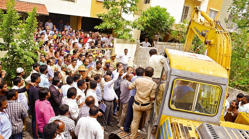 Residents of Suraksha Golden Palm Apartments protesting against the demolition of the apartment at Saraswathipuram in Bengaluru on Thursday (Photo: DC)