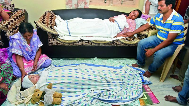 P. Radhika, lying on the sofa, watches the body of her daughter P. Ramya who succumbed to her injuries from a car accident, as her husband P. Venkat Ramana consoles her. Radhika was also seriously injured in the accident. (Photo: S. Surender Reddy)