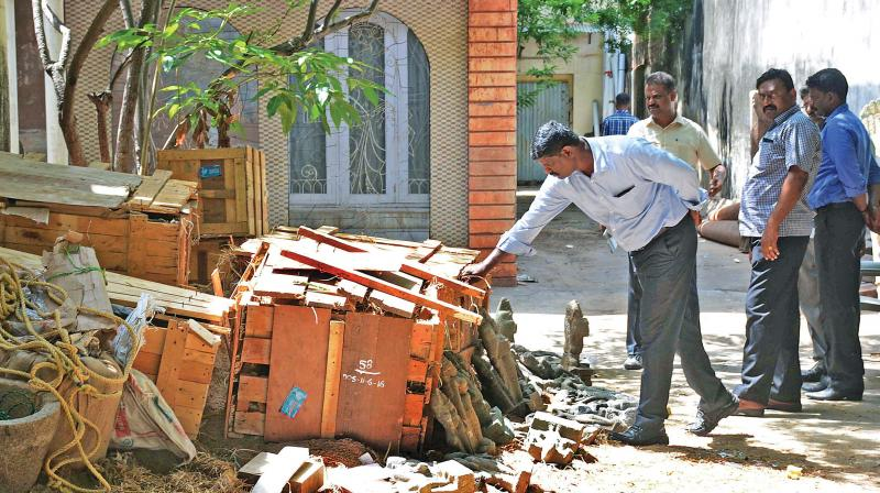 An official checking the wooden parcel box at the godown of Dheenadayalan, a suspected idol smuggler, in Alwarpet on Sunday. (Photo: DC)