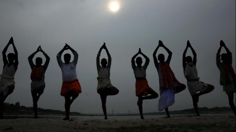 Local priests performing Yoga on the eve of International Yoga day in Allahabad. (Photo: PTI)