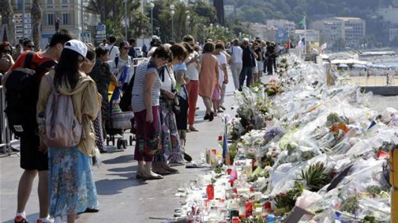 People look at flowers and messages placed along the beach of the Promenade des Anglais in Nice, southern France. (Photo: AP)