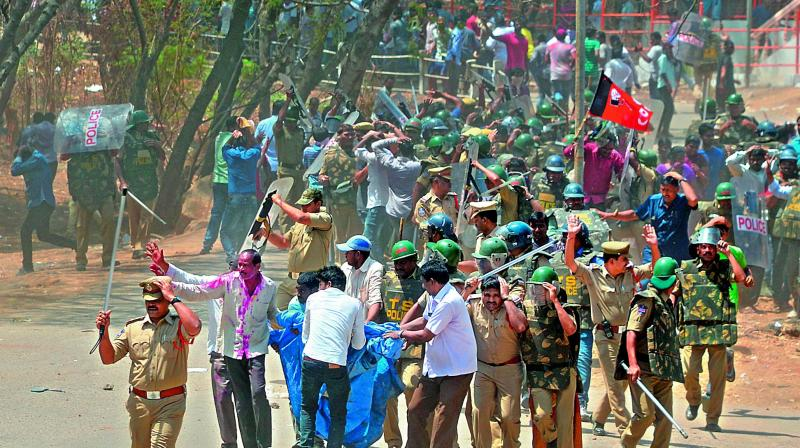 Police personnel are pelted with stones as they carry the body (in blue bag) out of OU campus on Wednesday. Some of the students were taken into custody