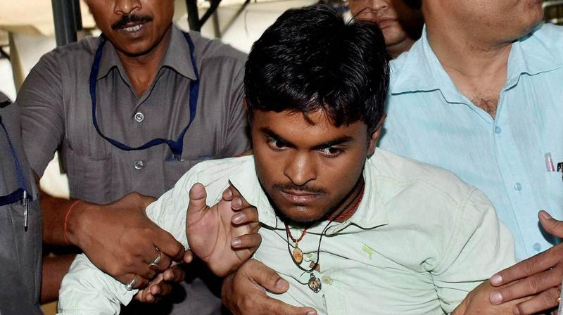 "Security personnel arrest youth who tried to fling his chappal towards Bihar Chief Minister Nitish Kumar during ""Janta Ka Darbar"" programme in Patna. (Photo: PTI)"