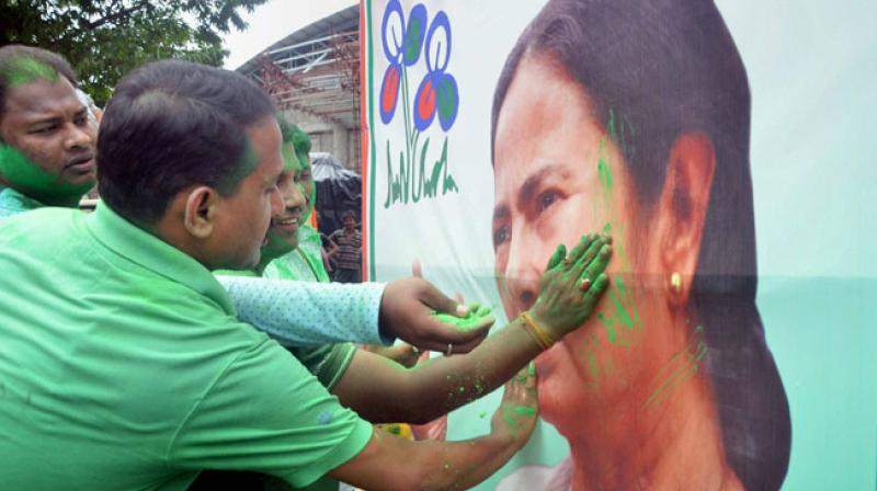 Trinamool Congress supporters smear colour on a poster of party chief Mamata Banerjee as they celebrate their win in West Bengal Assembly elections on Thursday. (Photo: PTI)
