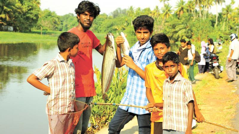 Residents with the fish they collected from Muttar river